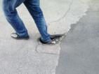 Un residente mette un piede nella fossa per mostrarne la profondità
