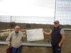 Giuliano Rogari e Luigi Carlini mostrano il cartello lavori del cantiere fuori al parco di sotto